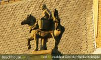detail oud gemeentehuis oostduinerke, beeld in blauwsteen van een paardenvisser